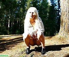 Naughty blonde pisses into a sandpit in forest